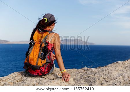 Woman back sits on mountain on background of sea