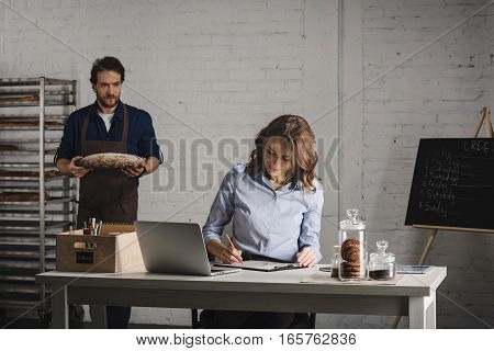 Man in apron showing loaf of fresh bread to the young woman making notes in bakehouse