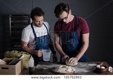 Male bakers in aprons preparing dough in bakery