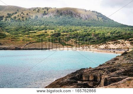Cute bay of Majorca island. View of Cala Mesquida with sand beach and azure turquoise sea from cape of Sa Cantera Mallorca Baleares Spain