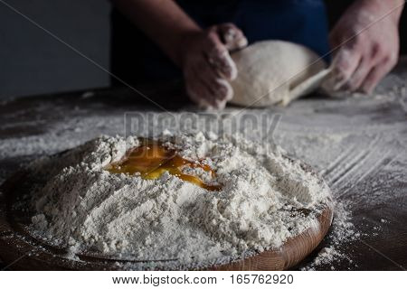 Partial view of baker kneading dough with flour and raw egg