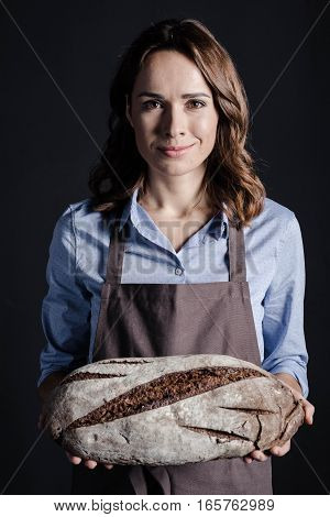 Young woman holding loaf of bread and looking at camera