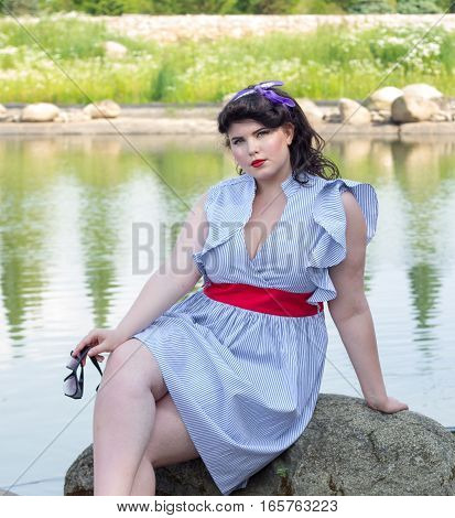 Young beautiful plus size model in dress sitting on a rock xxl woman portrait near the lake