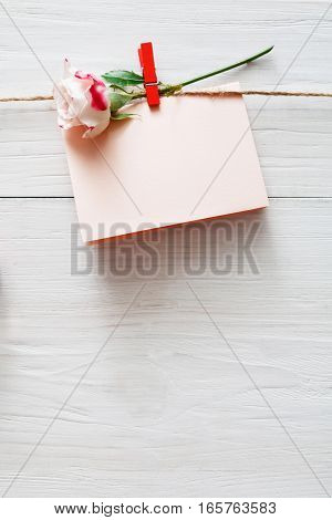 Valentine background, empty greeting card on clothespin on white rustic wood planks. Happy lovers day card mockup, copy space