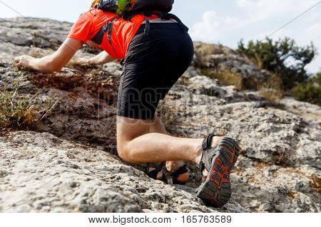 Man trying climb mountain with backpack on his back