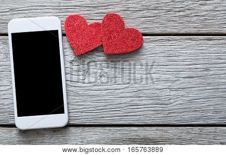 Valentine day internet messaging concept, online connection holiday background with copy space. Mobile phone on rustic wood with couple of red hearts, top view. Card and advertising mockup