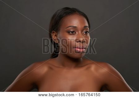 Gorgeous naked African-American young woman on grey background