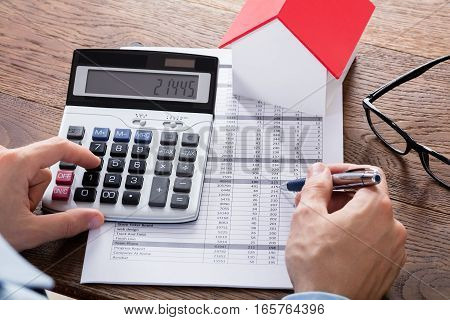Close-up Of A Person Hand Calculating A Real Estate Property Tax On Wooden Desk