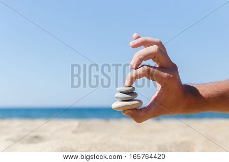 Photo of hand holds stones on beach
