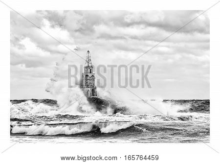 Stormy cloudy day. Dramatic sky and huge waves at the old Lighthouse