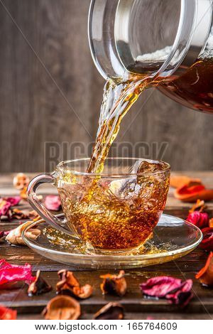 Cup of tea on saucer standing on wooden table with strewn with petals of dried flowers