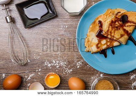 Two pancakes on blue plate with chocolate topping on wooden table