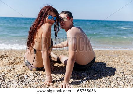 Young people in sunglasses sitting back at seashore during day