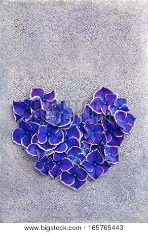 Purple hydrangea petals in the shape of a heart on a textured background.