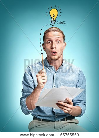 The surprised young man in blue shirt over blue studio background. Concept of idea, finds, inspiration