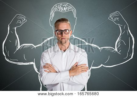 Conceptual Young Businessman Standing In Front Of Gray Background With Arm Muscles Drawing