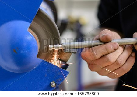 Engineer working on metal at a grinding machine - close-up