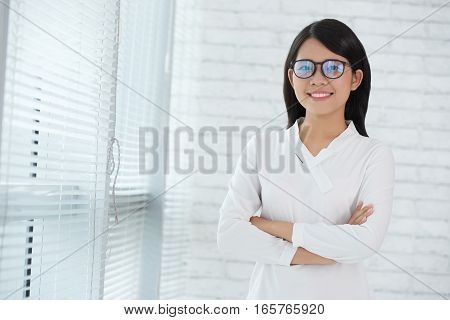 Pretty young Vietnamese business lady standing at window
