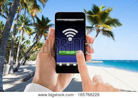 Close-up Of Man's Hand Connected WiFi On Mobile Phone At Beach. Internet Hotspot Coverage Concept