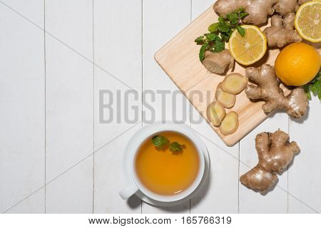 Cup of Ginger Tea with Lemon and Honey on a White Wooden Background.