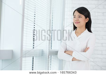 Confident young business woman looking through window