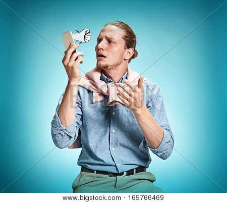 The young surprised caucasian businessman on blue background talking on cell phone. Concept of threatening and aggression
