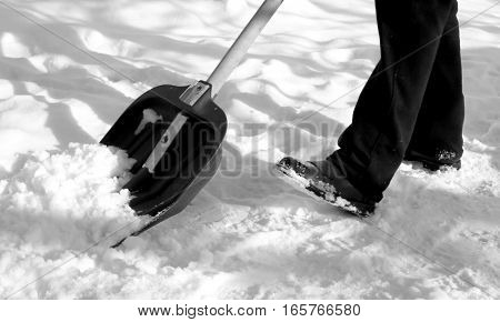 man removing snow with a shovel after snowfall