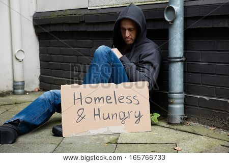 Homeless And Hungry Man Sitting On Street With Signboard