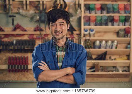 Portrait of smiling Vietnamese carpenter in his workshop