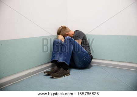 Man Sitting At The Corner Of His Room With Fear