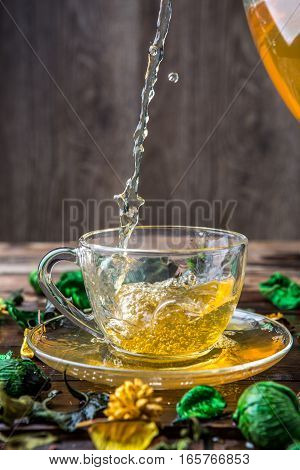 Green tea poured from jug into cup on table with dried flowers
