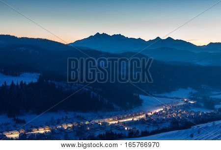 Twilight over the Tatra Mountains with the illuminated village in the valley.