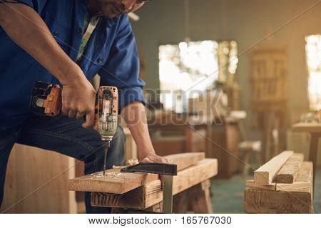 Cropped image of carpenter drilling wooden plank