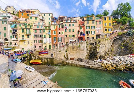 RIOMAGGIORE,LA SPEZIA,LIGURIA,NORTHERN ITALY - 9 August, 2015: View of the colourful houses on steep hills sea rocks beach laundry on balconies boats and tourists. Part of the Cinque Terre National Park and a UNESCO World Heritage Site.
