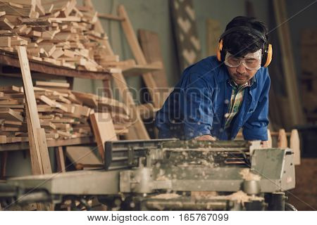 Carpenter in headphones and goggles using electrical buzz saw