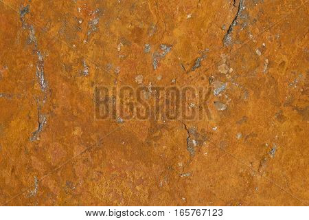 A flat stone plate rusting due to the iron ore in it. The rust pattern / texture has a naturally unique structure.