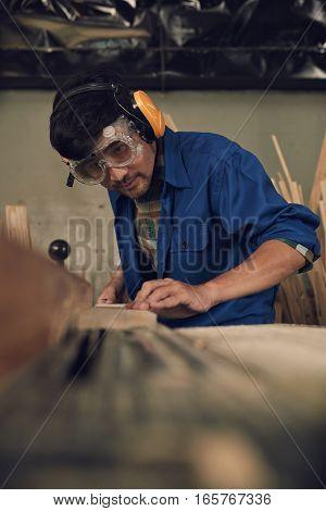 Carpenter in goggles cutting a piece of wood