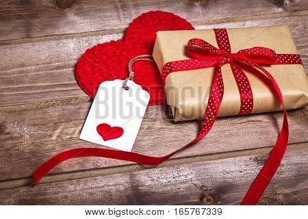 Wrapped vintage gift box with red ribbon bow on wooden background can use on valentine day mother day or celebrate love day . Beautiful  post card with paper hearts