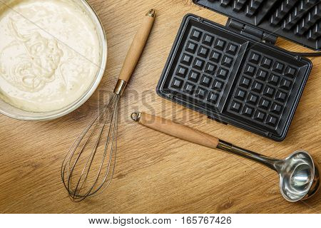 Making waffles at home - waffle iron and batter in bowl. Cooking background.