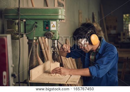 Asian young carpenter using drill press to mae hole in wooden plank