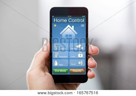 Close-up Of A Hand Holding Mobile Phone With Home Control System On Screen