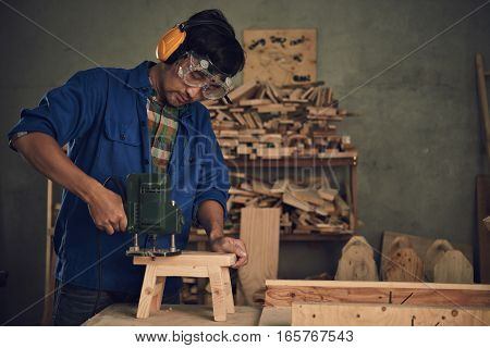 Carpenter using electric tool when making wooden chair