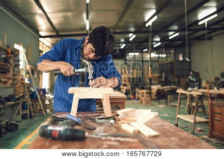 Carpenter hammering nail into wooden chair in workshop