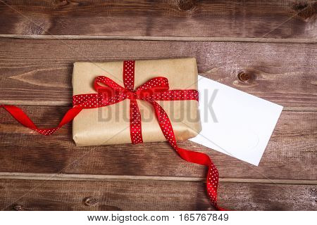 Wrapped vintage gift box with red ribbon bow and gift card aover the wooden table can use on valentine day mother day or celebrate love day .