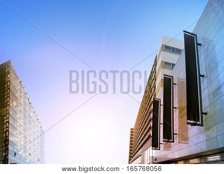 Blank black vertical banners on building facade, design mockup. Store flags mock up on the street. Outdoor flagpole template the side of the shop exterior. Three signages hanging on the wall.