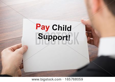 Close-up Of Person Hand Holding Pay Child Support Card In Envelope On Wooden Desk