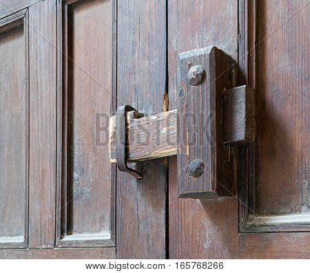 Closeup of a wooden aged latch over an ornate wooden door