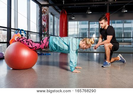 Sportwoman on fitball at gym with trainer
