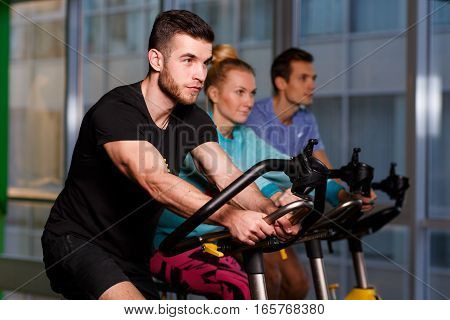 Sports people on stationary bike in fitness center in sport clothes