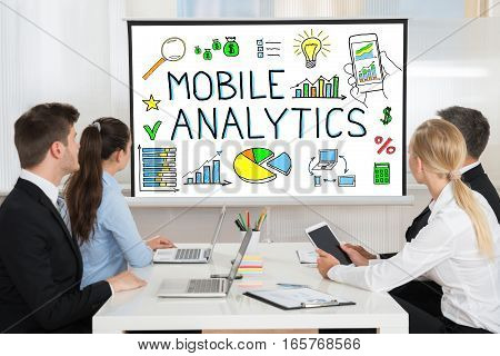 Businesspeople Looking At Mobile Analytic Concept On Projector Screen In Conference Room